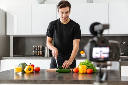 Handsome young man filming his video blog episode about healthy food cooking while standing at the kitchen
