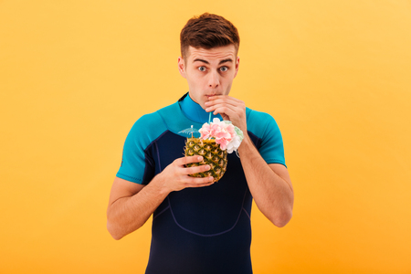 Image of Surprised surfer in wetsuit drinking cocktail and looking at the camera over yellow background Stock Photo