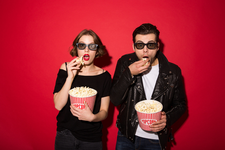 Surprised punk couple in eyeglasses eating popcorn and looking at the camera over red background Stock Photo