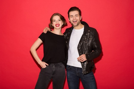 Image of Cheerful punk couple hugging and looking at the camera over red background