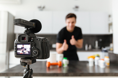 Smiling young man filming his video blog episode about healthy food additives while standing at the kitchen table and showing thumbs up gesture Stock fotó
