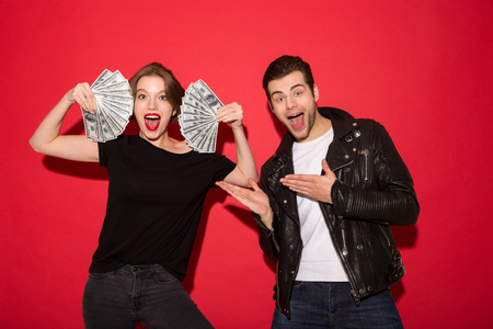 Happy punk woman showing the money while punk man posing near her and pointing at money over red background