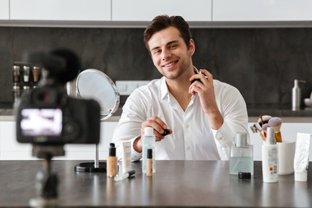 Smiling young man filming his video blog episode about new cosmetic products while sitting at the kitchen table and applying make-up Stock Photo
