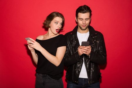 Smiling male punk using smartphone while woman peeps at him over red background