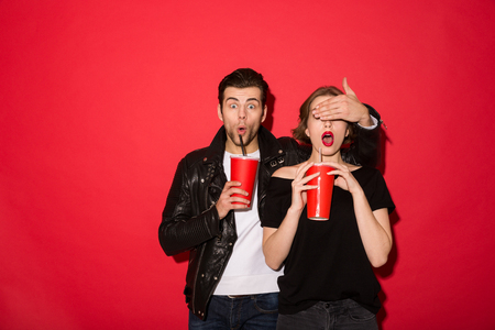Surprised punk man standing with soda while covering eyes to his girl over red background
