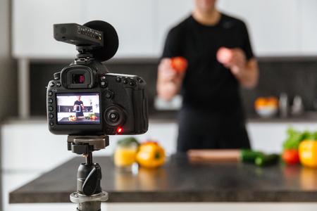 부엌에서 젊은 남자 블로거를 촬영 비디오 카메라의 가까이