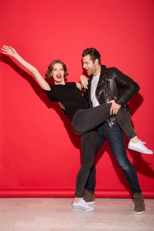 Volledig lengtebeeld van vrolijk punkpaar die samen over rode achtergrond dansen Stockfoto