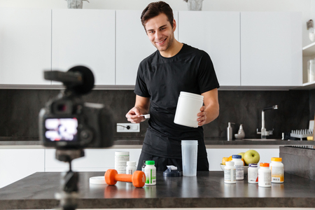 Happy young man filming his video blog episode about healthy food additives while standing at the kitchen table