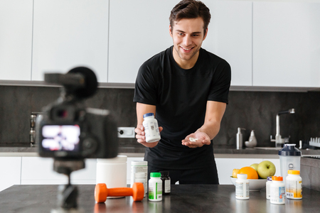 Cheerful young man filming his video blog episode about healthy food additives while standing at the kitchen table and showing pills