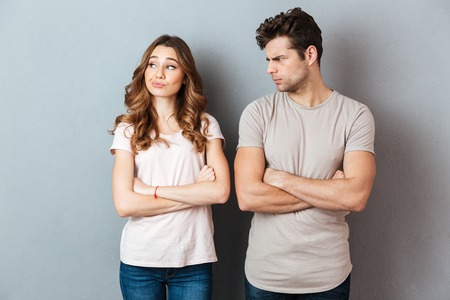 Disappointed young couple standing with arms folded over gray wall