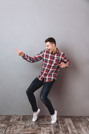 Full length image of Happy man in shirt and jeans dancing over gray background