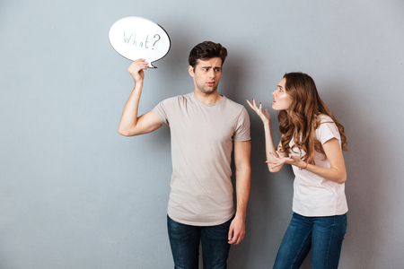 Portrait of a young couple having an argument, man holding speech bubble with what lettering isolated over gray wall Banque d'images