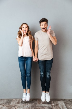 Full length portrait of an excited young couple holding hands and jumping over gray wall
