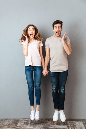 Full length portrait of a cheerful young couple holding hands and jumping over gray wall