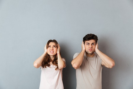 Portrait of an irritated couple covering ears while standing and looking up isolated over gray wall background