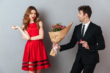 Retrato de un hombre feliz proponiendo a una niña insatisfecha con flores y un anillo de compromiso sobre fondo de pared gris