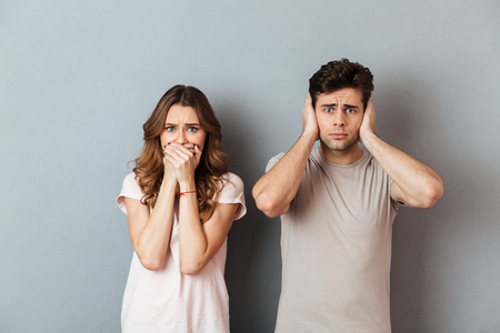 Portrait of an upset couple standing and covering ears and mouth isolated over gray wall background