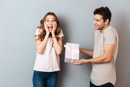 Portrait of a smiling man giving a present box to his girlfriend over gray wall