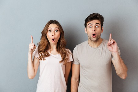 Portrait of a happy surprised couple standing and pointing fingers up at copy space isolated over gray wall background