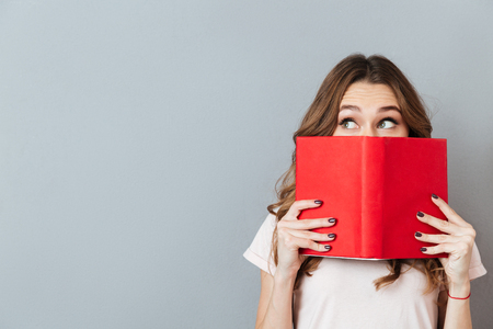 Portrait of a pretty young girl hiding behind an open book and looking away isolated over gray wall background Banco de Imagens