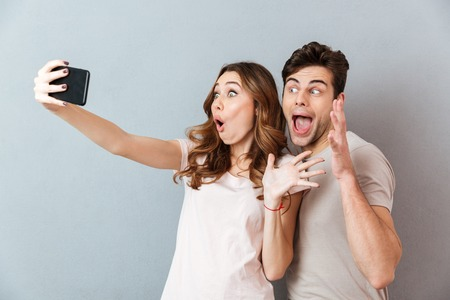 Portrait of an excited young couple standing and taking a selfie over gray wall