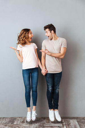 Full length portrait of a happy young couple holding hands and jumping over gray wall
