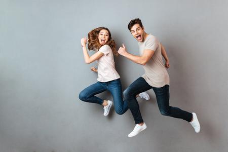 Portrait d'un jeune couple gai sautant et courant sur un mur gris