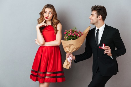 Portrait of a joyful man proposing to a unsatisfied girl with flowers and an engagement ring over gray wall background