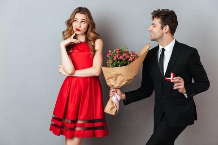 Porträt eines frohen Mannes, der zu einem unbefriedigten Mädchen mit Blumen und einem Verlobungsring über grauem Wandhintergrund vorschlägt