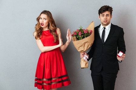 Portrait of a frustrated man proposing to a girl with flowers and an engagement ring and getting denied over gray wall background