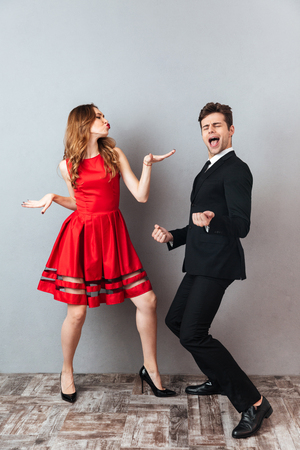 Full length portrait of a happy cheery couple dressed in formal wear dancing together and having fun over gray wall background Archivio Fotografico