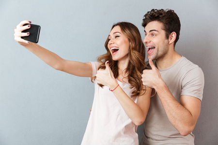 Portrait of a cheerful young couple showing thumbs up gesture while standing and taking a selfie over gray wall Stockfoto