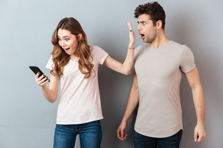 Portrait of a young couple standing with mobile phone, girl holding mobile phone while frustrated man standing near isolated over gray background