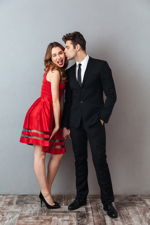Full length portrait of a happy smiling couple dressed in formal wear kissing while holding hands over gray wall background Stock Photo