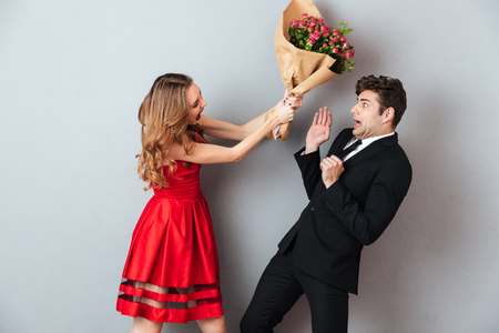 Portrait of a mad woman beating up a man with a flower bouquet over gray wall background