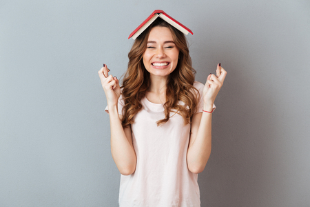 Portrait of a happy girl holding book on her head with crossed fingers for good luck isolated over gray wall background Archivio Fotografico