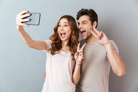 Portrait of a cheerful young couple showing peace gesture while standing and taking a selfie over gray wall Stockfoto