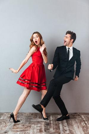 一緒に踊り、灰色の壁の背景の上に楽しみを持っているフォーマルな服を着た幸せな興奮したカップルの完全な長さの肖像画 写真素材