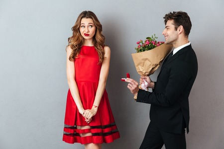 Portrait of a smiling man proposing to a girl with flowers and an engagement ring over gray wall background Stock Photo