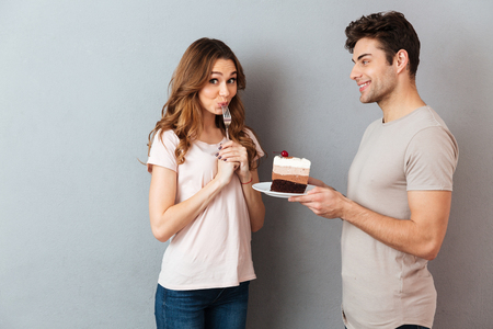 Portrait of a smiling man giving his girlfriend a piece of cake on a plate isolated over gray wall background Standard-Bild