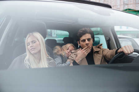 Image of yawning young man sitting in car with his sleeping wife and daughter. Looking aside. Banco de Imagens