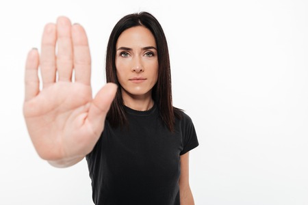 Portrait of a confident woman showing stop gesture with her palm isolated over white background Banque d'images - 91952519