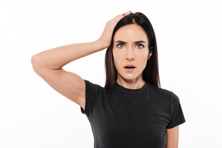 Portrait of a shocked upset woman holding hand at her head isolated over white background Stock Photo