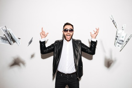 Portrait of a cheerful bearded man celebrating success while standing under the money rain isolated over white background