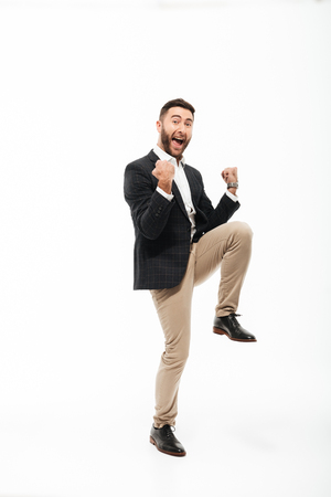 Full length portrait of a cheery happy man celebrating success isolated over white background