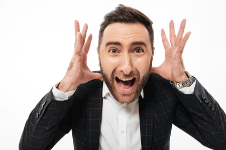 Close up portrait of a mad young bearded man looking at camera and shouting isolated over white background Stock Photo