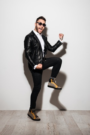 Full length portrait of a cheery happy man in leather jacket celebrating success while standing isolated over white background
