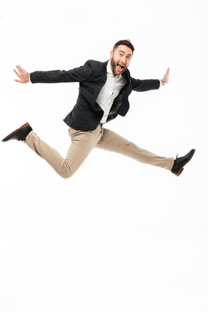 Full length portrait of a cheery happy man celebrating success while jumping isolated over white background