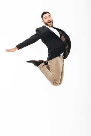 Full length portrait of an excited cheerful man celebrating success while jumping isolated over white background
