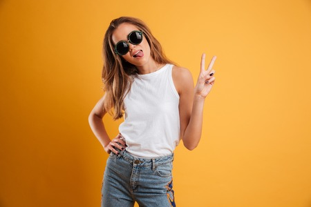 Portrait of a pretty funny girl in sunglasses showing peace gesture and looking at camera isolated over yellow background